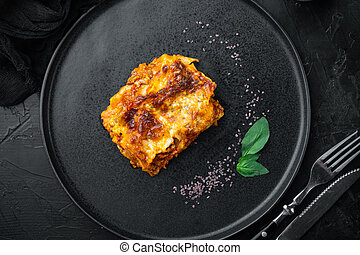 Italian Lasagne with tomato bolognese sauce and mince beef meat, on plate, on black stone background, top view, flat lay