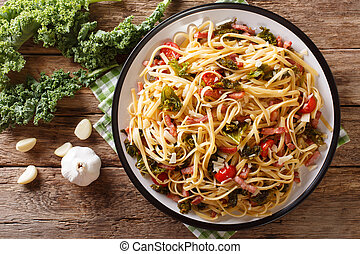 Italian lunch of pasta with cabbage kale, bacon, tomatoes and parmesan closeup. Horizontal top view