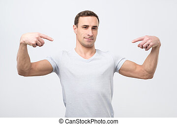 Italian man in white t-shirt, standing, pointing himself and...