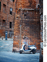 Italian motorcycle in an old alley of Siena