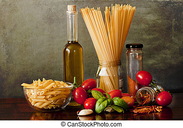 On the kitchen table an assorment of noodles and the ingredients for a tasty and spicy arrabbiata sauce : tomatoes, basil, chili, garlic, onion, olive oil. Healty, tasty, spicy.