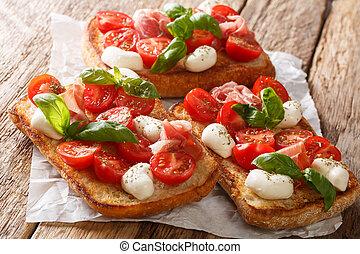 Italian open sandwiches with mozzarella, tomatoes, ham and basil closeup. horizontal