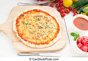 Italian original thin crust pizza Margherita with gazpacho soup and watermelon on side, and vegetables on background