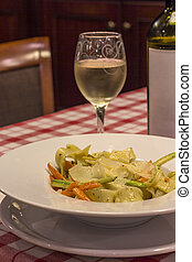 Italian pasta and glass of wine on the table in restaurant. close