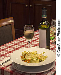 Italian pasta and glass of wine on the table in restaurant