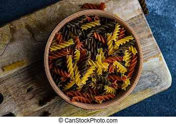Italian food concept with wooden bowl full of fusilli bucati pasta on concrete background with copy space