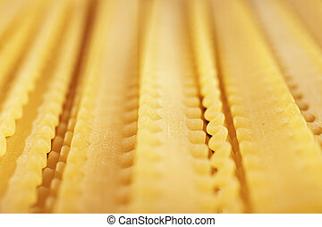 Raw Italian pasta called mafaldine , flat and wide pasta with wavy edges on both sides , beautiful abstract effect ,macro photography