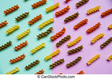 Italian pasta pattern on pink green background. Various colors of pasta viewed from above. Top view. Repetition. Full frame. Raw Italian pasta. Flat lay of uncooked pasta on double colorful background.