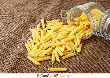 Italian pasta - penne in glass jar on brown background