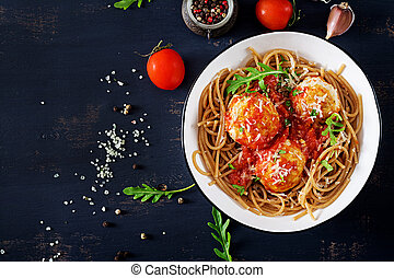 Italian pasta. Spaghetti with meatballs and parmesan cheese in bowl on dark rustic wood background. Dinner. Top view. Slow food concept