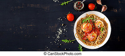 Italian pasta. Spaghetti with meatballs and parmesan cheese in bowl on dark rustic wood background. Dinner. Banner. Top view. Slow food concept