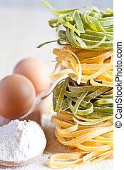 italian pasta tagliatelli, flour and eggs closeup on wooden...