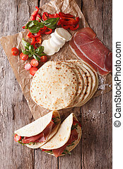 Italian piadina with ham, cheese and vegetables closeup. vertical top view