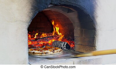 Italian pizza is cooking in a tradition a wood fired oven ...