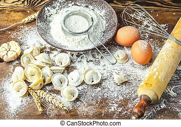 Italian ravioli, dumplings with meat and ingredients on dark...