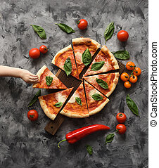 Italian rustic pizza Margherita as family meal. Baby hand reaching for piece of pizza on dark background