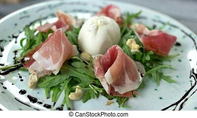 Italian salad close up. Arugula, prosciutto and nuts.
