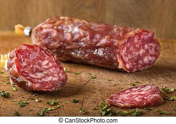 Italian salami on wooden cutting board with herbs