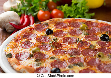 Italian salami pizza on table with vegetables
