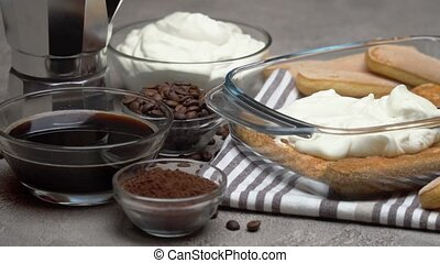 tiramisu dessert cooking - Traditional Italian Savoiardi ladyfingers Biscuits and cream in glass baking dish, coffe maker on concrete background or table
