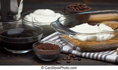 tiramisu dessert cooking - Traditional Italian Savoiardi ladyfingers Biscuits and cream in glass baking dish, coffe maker on wooden background or table