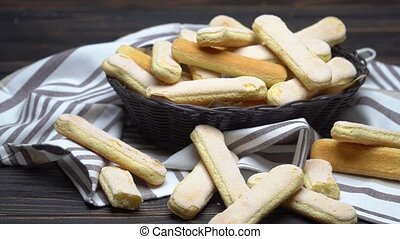 Italian Savoiardi ladyfingers Biscuits in basket on wooden...