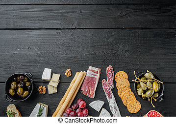 Italian snacks, meat cheese, herbs, on black wooden table, top view with copy space for text