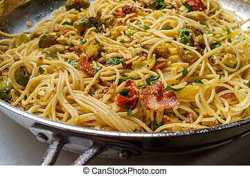 Cooking creamy Italian cuisine spaghetti alla carbonara with bacon and brussel sprouts - one pot dish