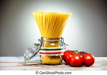 Uncooked dried Italian spaghetti tied with a ribbon in the colours of the national flag - red, white and green - standing in a glass jar with fresh ripe red tomatoes alongside
