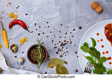 Italian spices. Bowl of black pepper, chilies and rosemary. Salad next to a bean meal on a table background. Copy space.