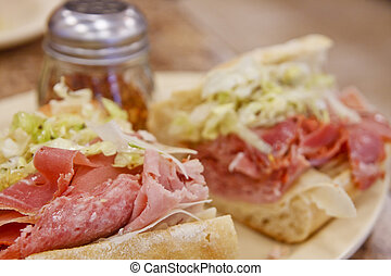 An italian sub sandwich dressed with lettuce and spices
