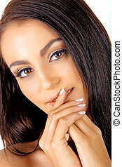 beautiful Italian tanned young woman with natural make-up and long hair holding hand next to her face