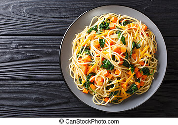 Italian vegetarian spaghetti with pumpkin, spinach and cheddar cheese close-up on a plate. Horizontal top view