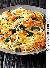 Italian vegetarian spaghetti with pumpkin, spinach and cheddar cheese close-up on a plate. vertical