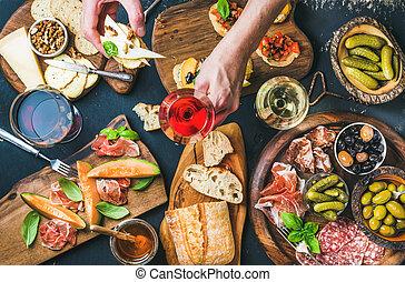 Italian wine snacks set, man's hand holding glass of rose