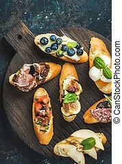 italienesche, crostini, mit, verschieden, toppings, auf, runder , hölzern, dienenden ausschuß