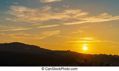 Italy. Fields, forests and mountains of Tuscany. The setting sun paints the clouds in wonderful colors. Time lapse 4K