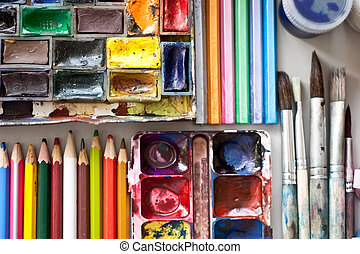 Items for drawing and art: watercolor paint, brushes, colored pencils.