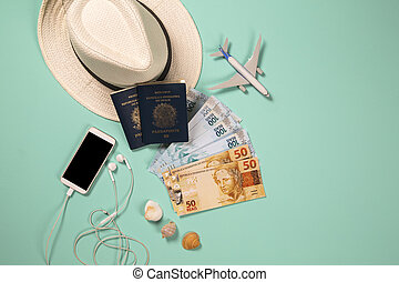 Items for summer vacation: telephone, passport, money and airplane. Blue background, top view