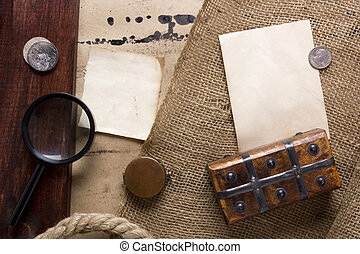 Items related to treasure - coins with a magnifying glass casket on the old background.
