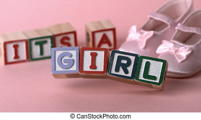 Its a girl message in letter blocks beside pink booties in...