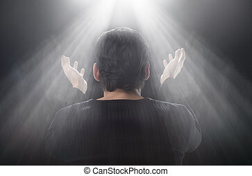 It's a miracle! Rear view of man standing in front of the window with his hands raised up