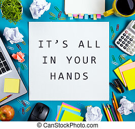 It's all in your hands. Office table desk with supplies, white blank note pad, cup, pen, pc, crumpled paper, flower on blue background. Top view
