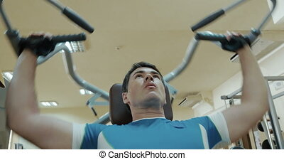 Low angle shot of a man exercising on shoulder press machine. His face expression showing that every next movement getting harder