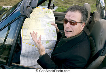 Man pulled off to the side of the road, holding a map, trying to get directions with a look of slight bewilderment on his face.