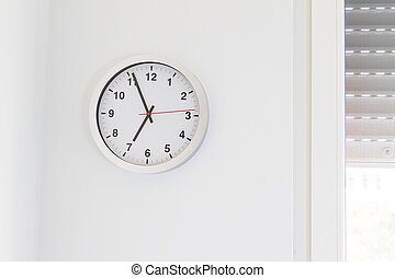 it's seven o'clock already, time to wake up for breakfast, modern white metallic alarm clock on modern white wall background