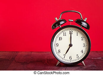 it's seven o'clock already, time to wake up for love, vintage old black metallic alarm clock on red background