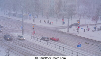 It's snowing in the city, the road, cars driving on snowy road