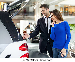 It?s so roomy inside. Handsome young car salesman showing...