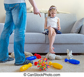 Its time to clean up your toys! Little girl playing with tablet pc, ignoring her father.